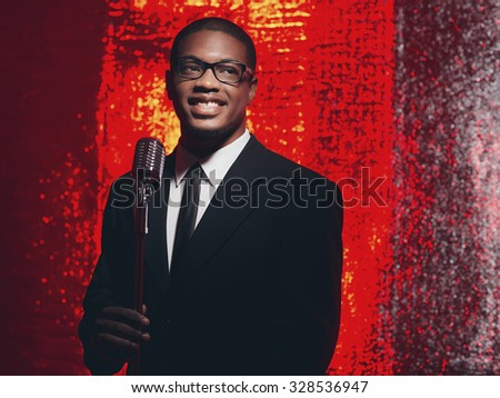 Retro 50s male hispanic singer in black suit and tie. Red reflections background. - stock photo