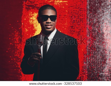 Retro 1950s male latin american singer with sunglasses in black suit and tie. Red reflections background. - stock photo
