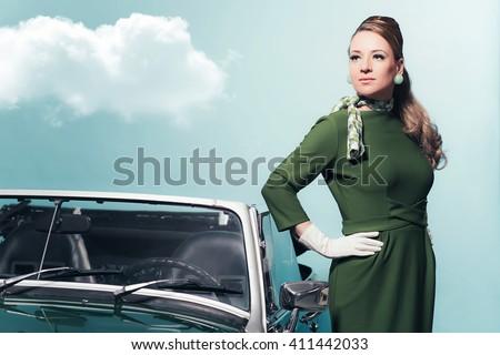 Retro 1960s woman in green dress standing next sportscar. - stock photo