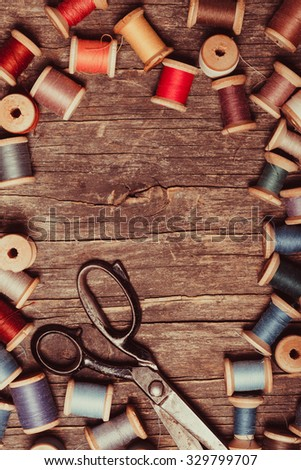 Retro scissors, textile and sewing threads on the wooden table with copy space - stock photo