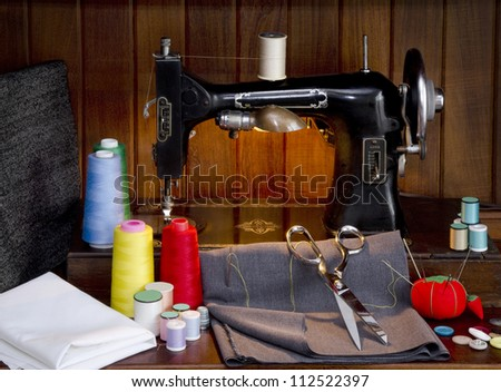 Retro sewing machine with sewing paraphernalia including thread, fabric, sewing needles, pin cushion, buttons scissors and thimble - stock photo