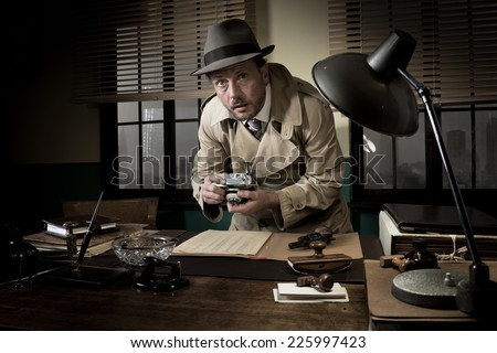 Retro spy agent caught photographing important documents on office desk, 1950s style. - stock photo