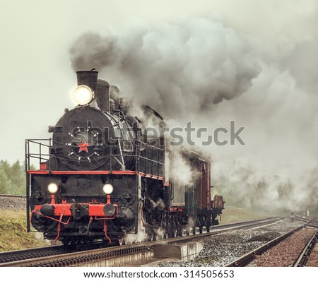 Retro steam freight train under the pouring rain. - stock photo