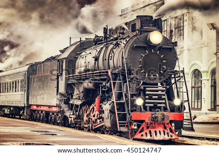 Retro steam train departs from the station. - stock photo