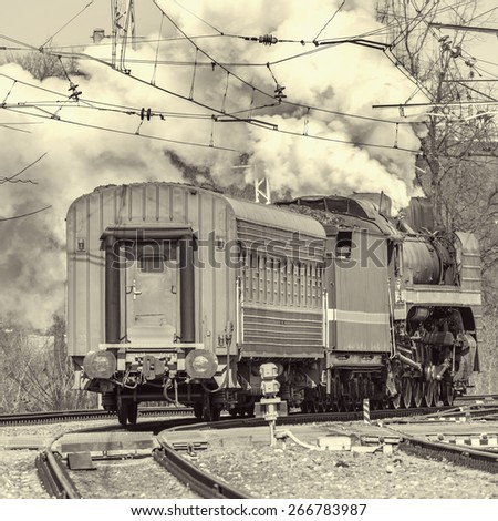 Retro steam train departs from the station. Vintage image. - stock photo