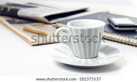 retro style coffee cup with notepad phone and newspapers on office desk - stock photo