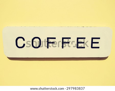 "Retro style image of a black text ""coffee"" white signboard hanging on soft yellow wall. - stock photo"