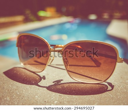 Retro Style Image Of Sunglasses Beside A Swimming Pool - stock photo