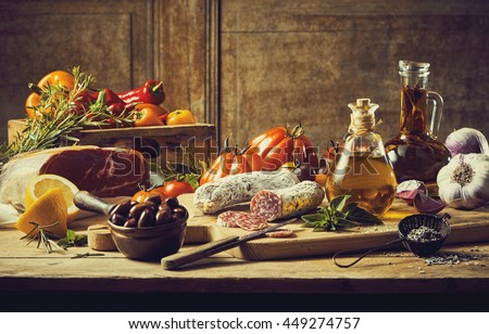 Retro style kitchen still life with fresh vegetable ingredients, cuts of cold meat and salami, condiments and olive oil on a rustic wooden table - stock photo