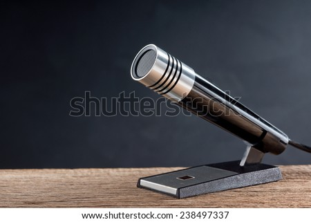 retro style microphone on old wood table with art dark background space - stock photo