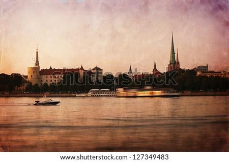 Retro style panorama of old Riga at dusk. Latvia - stock photo