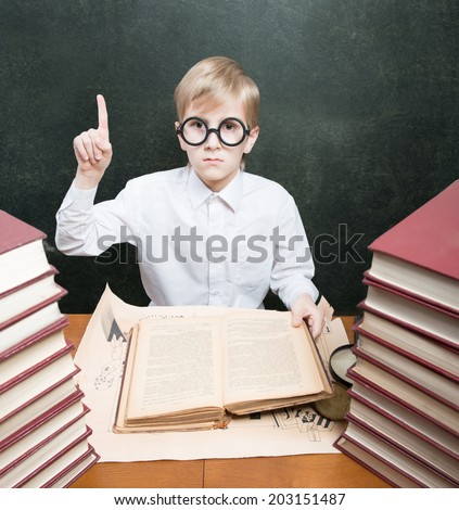 Retro style portrait of a boy with an old book raising the index finger up - stock photo