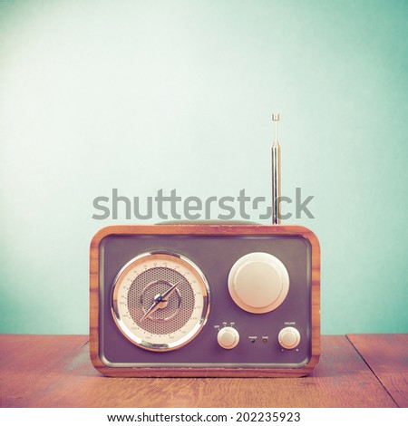 Retro style radio receiver on table front mint green background - stock photo
