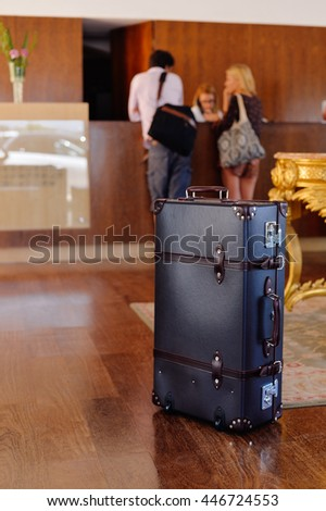Retro style suitcase trunk ready for travel, background with defocused couple at the reception desk - stock photo