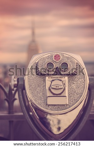 Retro style toned image of coin operated binoculars viewing New York City and Empire State Building - stock photo