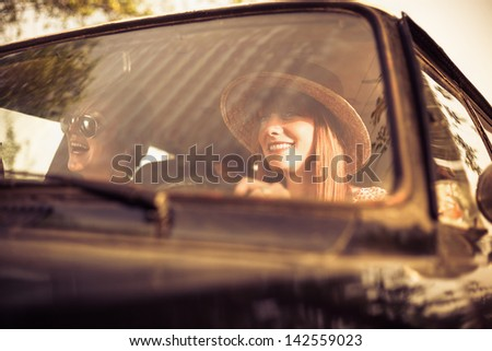 Retro style woman driving old timer car. Traveling with her friends. - stock photo