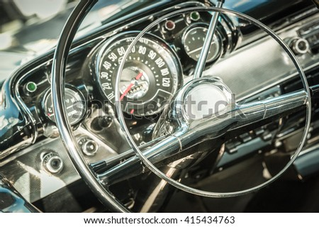 retro styled classic car steering wheel and dashboard dials - stock photo