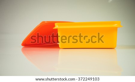 Retro styled food carrier or retro color plastic lunch box. Slightly de-focused and close-up shot. Copy space - stock photo