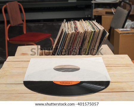 Retro styled image of a collection of old vinyl record lp's with sleeves on a wooden background. Browsing through vinyl records collection. Music background. Copy space. - stock photo