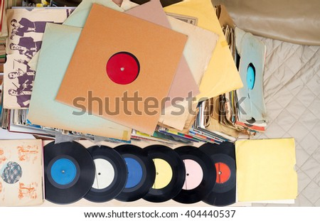 Retro styled image of a collection of old vinyl record lp's with sleeves on a wooden background.  Copy space. Top view. - stock photo