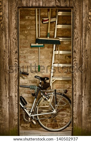 Retro styled image of a shed with a bicycle and garden tools inside - stock photo