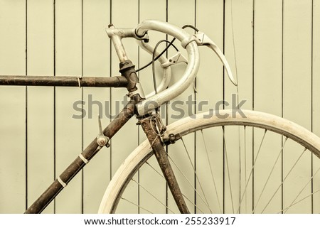 Retro styled image of a vintage rusted racing bicycle in front of a wooden wall - stock photo