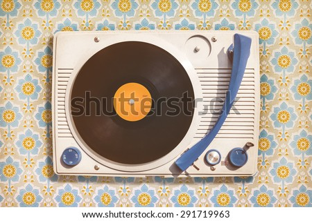 Retro styled image of an old record player on top of flower wallpaper - stock photo