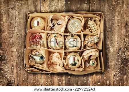 Retro styled image of vintage Christmas decoration in a box on a wooden floor - stock photo
