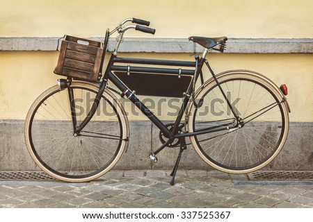 Retro styled sepia image of a vintage black transport bicycle with wooden crate - stock photo