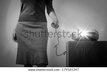 Retro styled woman operating a slide projector with a wired remote control and lens flare from projector light in black and white - stock photo