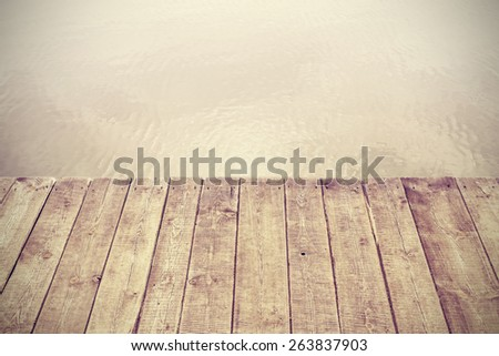 Retro stylized picture of wooden boards and lake, background with space for text. - stock photo
