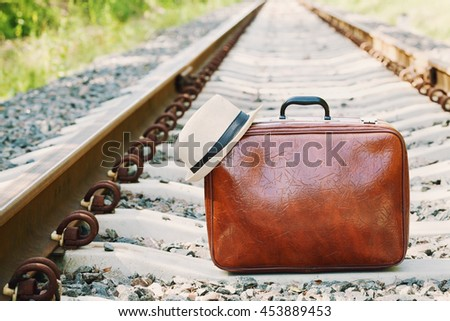 Retro suitcase and hat standing on the railway on a sunny day. Holidays, vacation, travel and trip. - stock photo