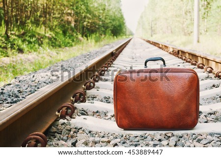 Retro suitcase standing on the railway on a sunny day. Holidays, vacation, travel and trip. - stock photo