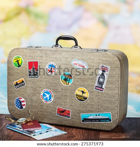 retro suitcase with stikkers on the floor against the backdrop of a world map - stock photo