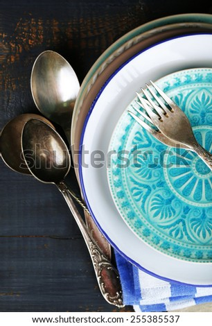 Retro tableware and napkins on old wooden table, close up - stock photo