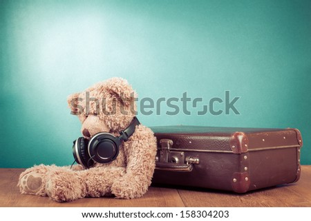 Retro teddy bear with headphones sitting near old suit case concept - stock photo