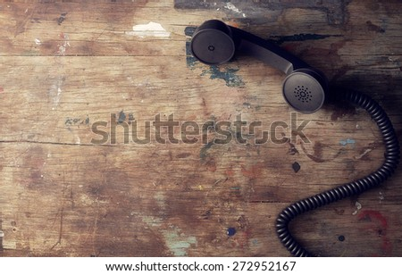 Retro telephone reciever on old wooden table background - stock photo