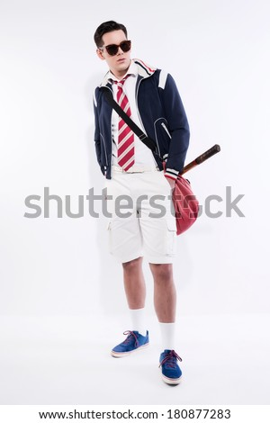 Retro tennis fashion man with sunglasses holding a red bag with vintage wooden racket. Studio shot against white. - stock photo