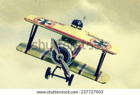 retro tin toy plain with clouds and sky , retro styled image . - stock photo