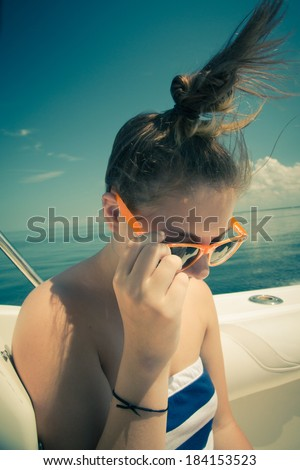 Retro toned image of girl on boat with hair blowing - stock photo