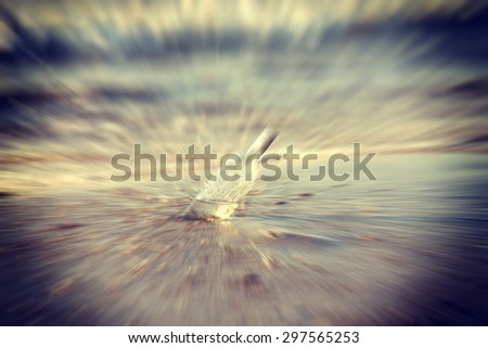 Retro toned motion blurred bottle of vodka in water, alcohol problem concept. - stock photo
