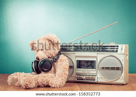 Retro toy Teddy Bear and radio recorder in front mint background - stock photo