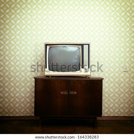 Retro tv with wooden case in room with vintage wallpaper and parquet, toned - stock photo