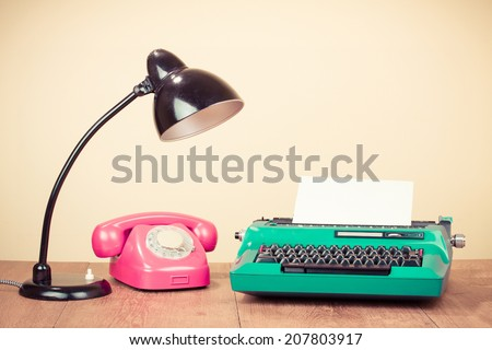 Retro typewriter with paper, old desk lamp, rotary telephone on table - stock photo