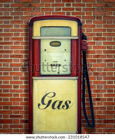 Retro Vintage Americana Gas Station Pump Against Red Brick Wall - stock photo
