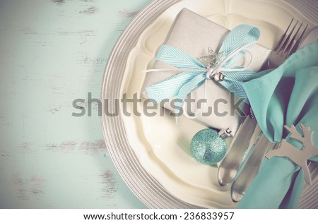 Retro vintage Christmas table place settings in aqua blue, silver and white theme, on recycled wood background. - stock photo