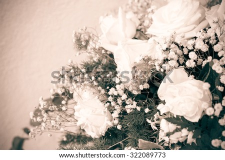 Retro vintage edit of a bouquet of white roses and white flowers, artistic sepia vintage selective soft focus edit with copy space for text. - stock photo