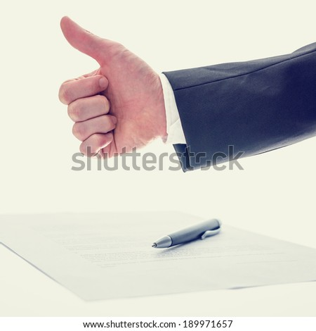 Retro vintage effect image of the arm of a businessman giving a thumbs up gesture of approval , success and agreement with a document and pen below conceptual of a business deal. - stock photo