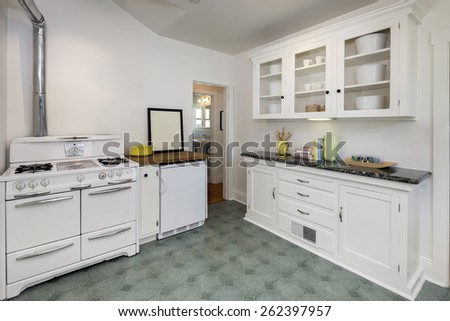 Retro, Vintage kitchen with white appliances, refrigerator, oven, decorated black granite ornamented counter top and cabinets. - stock photo