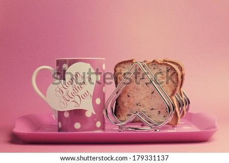 Retro vintage old fashion style Happy Mothers Day breakfast with toast and polka dot coffee tea cup and heart shape rack on faded pink background. - stock photo